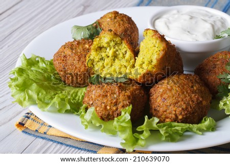 falafel with lettuce and tzatziki sauce closeup on a white plate on the table. horizontal  - stock photo