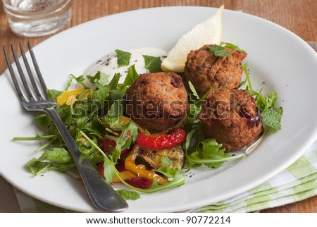 Falafels with rocket and roasted vegetables on a plate