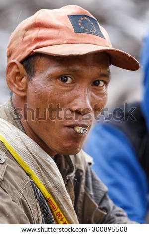 FALAM, MYANMAR - JUNE 17 2015: Local man smoking burmese cigar (cheroot) at the start of the monsoon season in the recently opened to tourists Chin State region of Western Myanmar (Burma) - stock photo