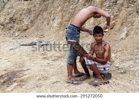 FALAM, MYANMAR - JUNE 17 2015: Local young men cut hair in the recently opened to foreigners area of Chin State - western Myanmar (Burma)