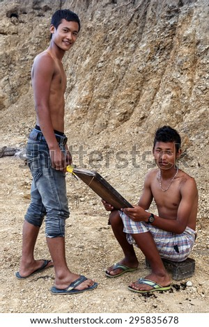 FALAM, MYANMAR - JUNE 17 2015: Local young men cut hair in the recently opened to foreigners area of Chin State - western Myanmar (Burma) - stock photo