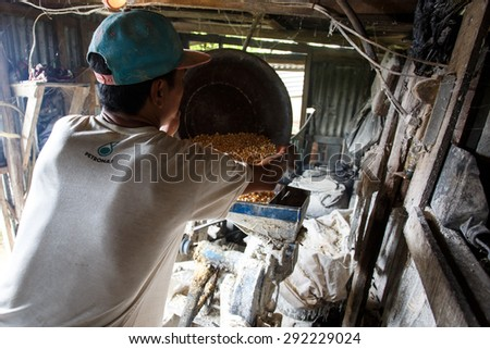 FALAM, MYANMAR - JUNE 17 2015: Making pig feed using a grinding machine in the town of Falam in Chin State, Myanmar. - stock photo