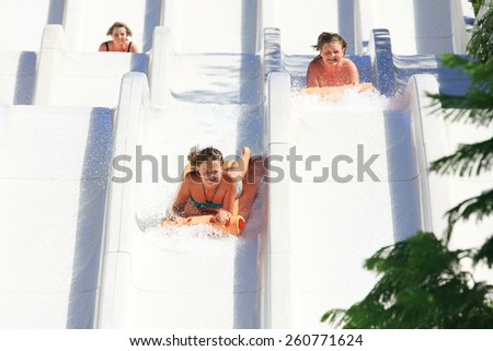 Faliraki,Rhodes,Greece-August,12,2015:Two young girls with mom on the mat racer slide in Water park,Mat racer slide is very popular for Youth and adults person in the Water Park - stock photo