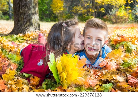 Fall. Brother and sister with leaves in autumn park - stock photo