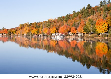 Fall Colors Reflected in Calm Lake - brilliant fall colors reflected in a smooth, calm lake.  Photographed in morning light. - stock photo