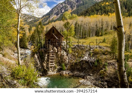 Fall colors surrounding abandoned historic landmark the Crystal Mill located on the Crystal River above the town of Marble Colorado on fall afternoon - stock photo