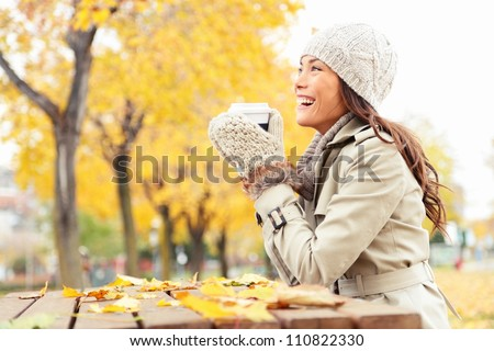 Fall concept - autumn woman drinking coffee on park bench under fall foliage. Beautiful young modern woman smiling happy and cheerful in trench coat. - stock photo