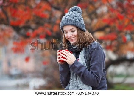 Fall concept - autumn woman drinking coffee on park bench under fall foliage. Beautiful young modern woman smiling happy and cheerful