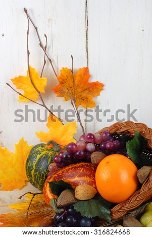 Fall cornucopia containing orange, grapes, squashes and nuts with autumn leaves scattered around.  Good for fall, autumnal equinox, Halloween or Thanksgiving. Vertical composition with copy space  - stock photo