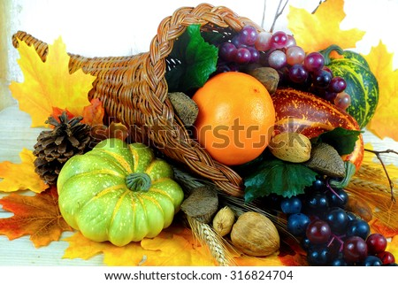 Fall cornucopia overflowing with orange, grapes, squashes and nuts with autumn leaves scattered around.  Good for fall, autumnal equinox, Halloween or Thanksgiving   - stock photo