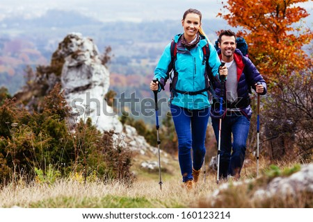 Fall. Couple Backpackers hiking on the path in mountains during autumn. - stock photo