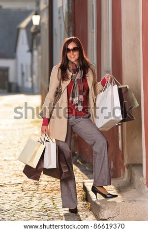 Fall elegant woman carrying shopping bags walking city street sunset - stock photo
