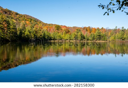 Fall foliage and its reflection at Equinox pond in Vermont - stock photo