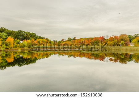 Fall Foliage and Reflection in Water with Cloudy Sky - stock photo