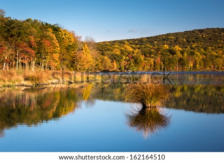 Fall foliage colors reflected in Silver Mine Lake (UpState New York) on a sunny afternoon. - stock photo