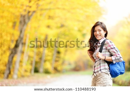 Fall hiking girl. Woman hiker portrait in forest in autumn colors. Beautiful young mixed race female on hike. Image from Mont Sutton, Quebec, Canada. - stock photo