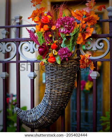 Fall holiday basket of flowers hanging on gate entry. - stock photo