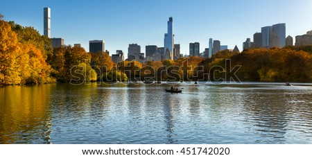 Fall in Central Park at The Lake with Midtown Manhattan skyscrapers. Panoramic afternoon cityscape view with colorful fall foliage. Manhattan, New York City - stock photo