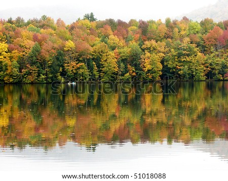 Fall leaves at a pond with canoe - stock photo