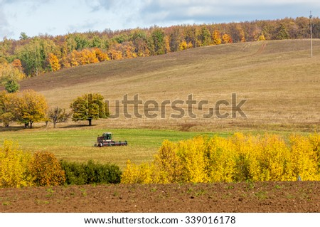 Fall plowed field, a large willow tree harvester mowing grass - stock photo