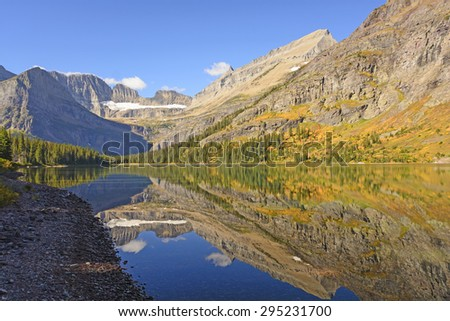 Fall Reflections in Early Morning on Lake Josephine in Glacier National Park in Montana - stock photo