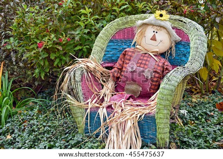fall scarecrow sitting in a wicker chair in garden