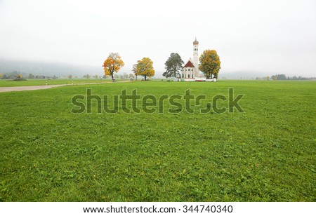 Fall scenery of Bavarian countryside in Schwangau, Germany ~ St. Coloman Church and beautiful autumn trees in the green meadow on a foggy morning - stock photo