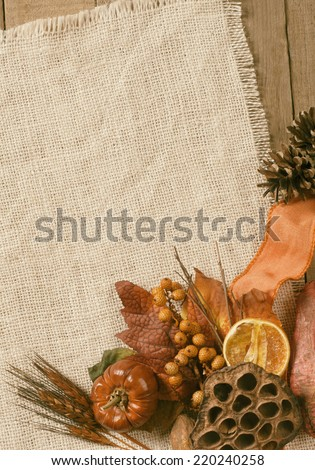 Fall Season card with Nature Elements in Rustic Setting with Burlap and old wood background from above with empty room or space for copy, text, your words, vertical.  Faded warm, sepia tones - stock photo