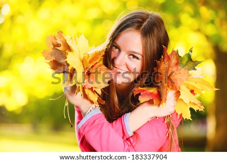 Fall season. Portrait of happy girl young woman holding colorful leaves in autumnal park forest. Outdoor.