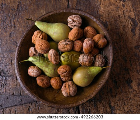 Fall still life with a bowl of pears and walnuts on a grunge wooden background