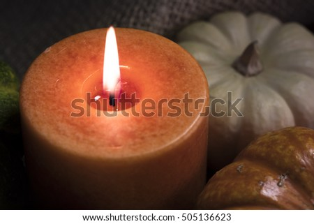 Fall theme close up of orange candle burning with gourds