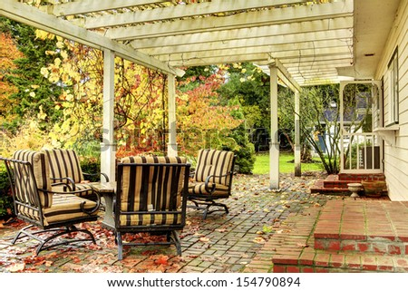 Fall trees and back porch with furniture. - stock photo
