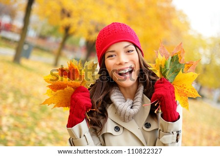 Fall woman happy and bliss in autumn city forest park holding colorful fall leaves smiling happy and joyful wearing tuque and knit gloves. Pretty multiracial Asian and Caucasian girl model.