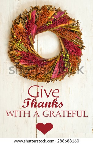 Fall wreath hanging on rustic, white painted wooden wall with removable Thanksgiving message. Dried wreath has fall colors of magenta, green, gold and orange - stock photo