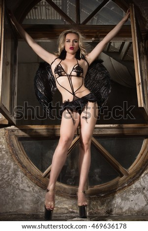 Fallen black angel with wings. Sexual woman dressed black lingerie.