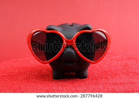 Fallen in love black piggy bank with red heart sunglasses standing on red sand in front of red background - stock photo