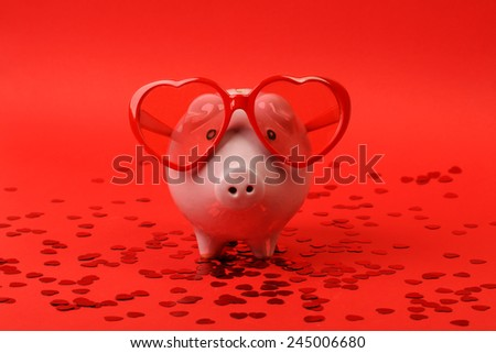 Fallen in love piggy bank with red heart sunglasses standing on red background with red shining heart glitters - stock photo