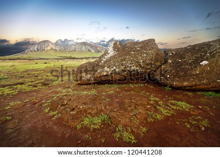 Fallen moai on red earth with mountain on background - stock photo