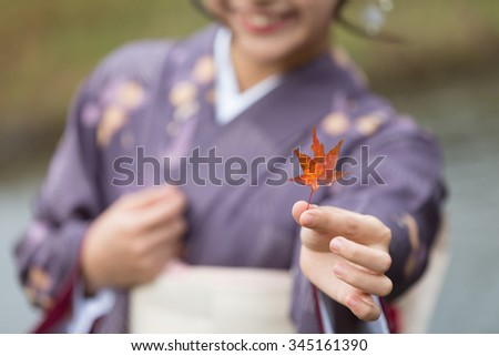 Fallen orange-red leaf of Japanese maple (momiji) shown by a smiling Japanese girl in the background, wearing a purple seasonal kimono