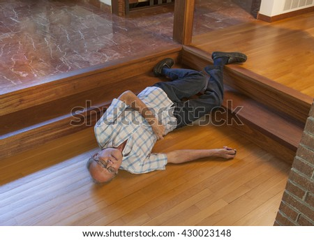 Fallen senior man activating an electronic device in his hand to call for help - stock photo