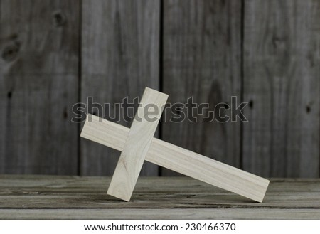Fallen wooden cross with rustic wood background; Easter, Christmas, Memorial Day and religious background with copy space