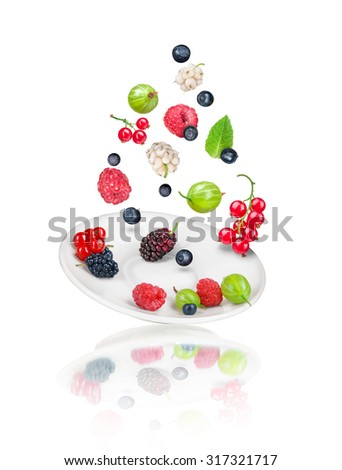 falling berries on saucer isolated on white background