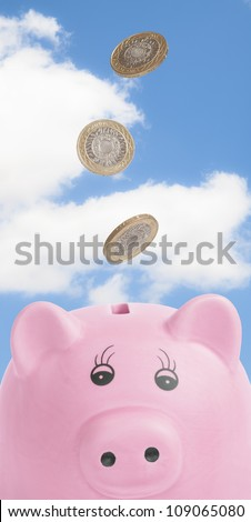 Falling British coins into pig money box against blue sky - stock photo