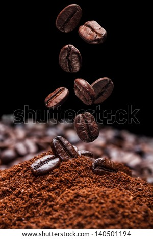 Falling brown roasted coffee beans - stock photo