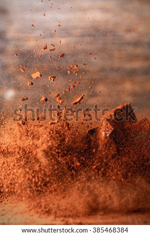 Falling cocoa powder on wooden table - stock photo