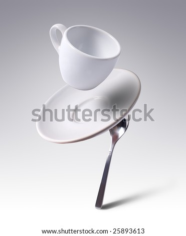 falling coffee cup with spoon and saucer - stock photo