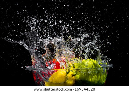 Falling colored vegetables to tank with water - stock photo