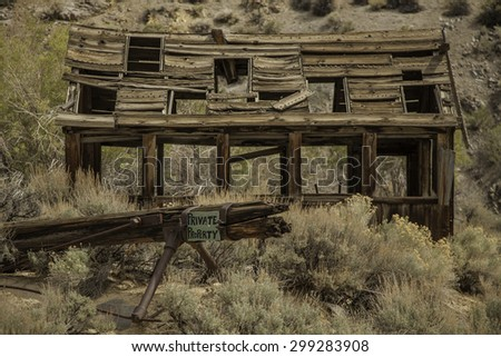 Falling down old shack with private property sign in Nevada desert. - stock photo