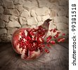 Falling down ripe pomegranate with cracks and splashes of juice and seeds - stock photo