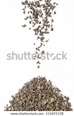 Falling dried green tea leaves isolated on white background